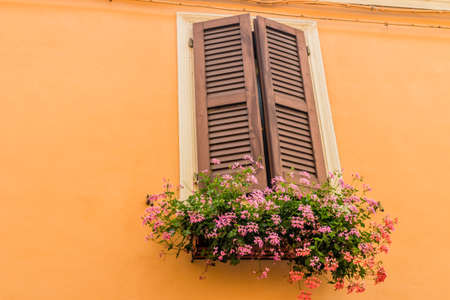 red shutters: Window with wooden shutters and pots of red and pink geraniums hanging on orange wall