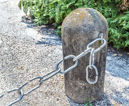 defines: the link in the chain is opening: this weak link defines the real strength of this steel chain linked to bollard
