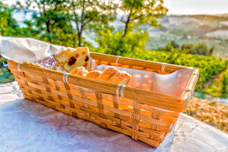 farmlands: dinner in the country, bread basket on a table with vineyards, farmlands and green vegetation of the countryside in the background