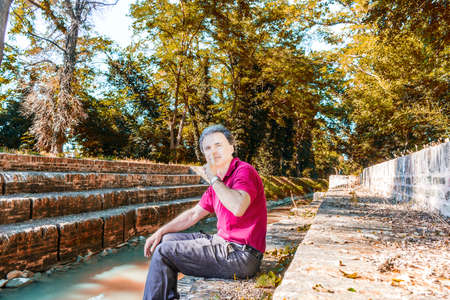 charismatic: Charismatic and handsome Caucasian sportsman of forty with grey hair wearing red polo shirt and dark linen trousers invites you to be quiet while sitting on the ancient medieval steps of Mill Canal in Emilia Romagna in Italy Stock Photo