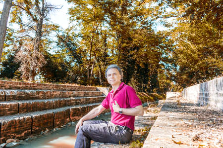 indicates: Charismatic and handsome Caucasian sportsman of forty with grey hair wearing red polo shirt and dark linen trousers indicates himself  sitting on the ancient medieval steps of Mill Canal in Emilia Romagna in Italy