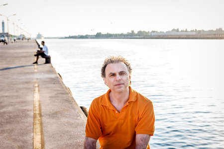 40 years old: Classy  40 years old sportsman with three-day beard and salt and pepper hair wearing an orange polo shirt while he is sitting on the pier and resting
