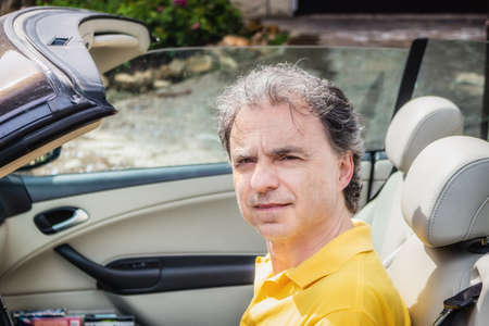 40 years: Side view of classy  40 years old sportsman with three-day beard and salt and pepper hair wearing a yellow polo shirt while he is driving a dark brown car in residential neighborhood