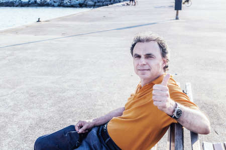 40 years: Classy  40 years old sportsman with three-day beard and salt and pepper hair wearing an orange polo shirt while he is sitting on a bench on the pier and showing thumb up