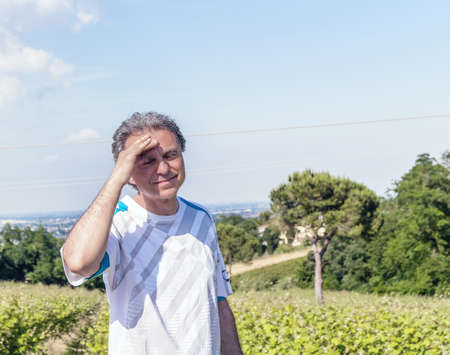 Handsome 40 years old man with salt pepper hair dressed with sports shirt is holding his head in the cultivated fields of Italian countryside: he seems to have headache Stock Photo