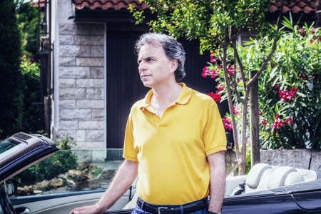 40 years: Classy 40 years old sportsman with three-day beard and salt and pepper hair wearing a yellow polo shirt while he is sitting on the door of a dark brown cabriolet car in residential neighborhood Stock Photo