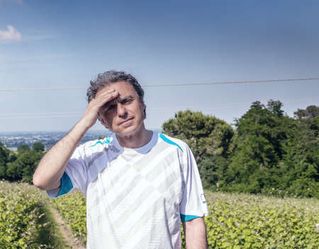 40 years old man: Handsome 40 years old man with salt pepper hair dressed with sports shirt is holding his head in the cultivated fields of Italian countryside: he seems to have headache Stock Photo