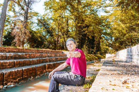 charismatic: Charismatic and handsome Caucasian sportsman of forty with grey hair wearing red polo shirt and dark linen trousers points while  sitting on the ancient medieval steps of Mill Canal in Emilia Romagna in Italy