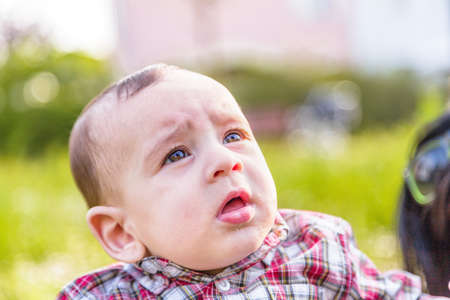 gape: Cute 6 months old baby with Light brown hair in red checkered shirt and beige pants is gaping Stock Photo