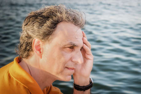 40 years: Classy  40 years old sportsman with three-day beard and salt and pepper hair wearing an orange polo shirt while he is thinking in front of the sea