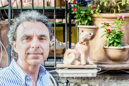 soft skin: middle-aged man  with soft skin in a striped shirt in front of pots of flowers in Italian village market Stock Photo