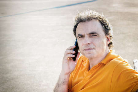40 years old: Classy  40 years old sportsman with three-day beard and salt and pepper hair wearing an orange polo shirt while he is sitting on a bench on the pier and talking on a mobile phone
