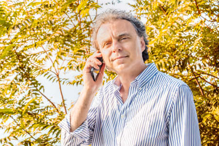 soft skin: middle-aged man  with soft skin in a striped shirt talking on cell phone in front of green foliage at sunset in the Italian countryside