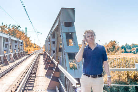40 years old man: Caucasian 40 years old man, elegant and sporty dressing a blue polo shirt,  is talking on the mobile phone next to railroad tracks in the Italian countryside in summer