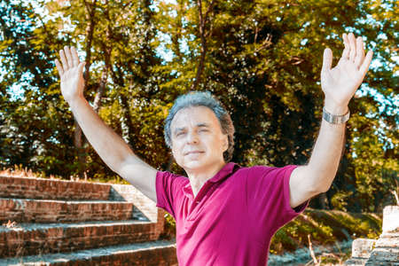 charismatic: Charismatic and handsome Caucasian sportsman of forty with grey hair wearing red polo shirt and dark linen trousers is raising arms while sitting on the ancient medieval steps of Mill Canal in Emilia Romagna in Italy