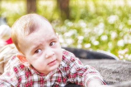 pelo castaño claro: Cara divertida del bebé lindo 6 meses de edad con el pelo marrón claro en camisa a cuadros roja y pantalones de color beige: él está mordiéndose los labios y las mejillas puffing