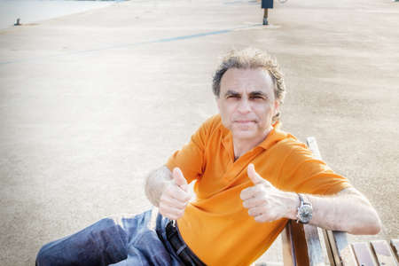 40 years old: Classy  40 years old sportsman with three-day beard and salt and pepper hair wearing an orange polo shirt while he is sitting on a bench on the pier and showing thumbs up