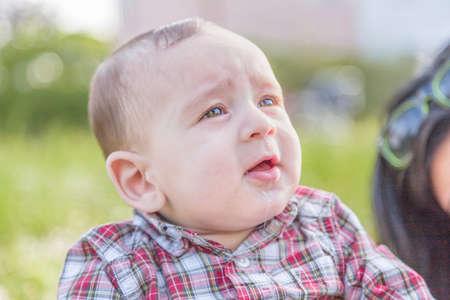 cabello casta�o claro: La felicidad inocente de un beb� de 6 meses linda con el pelo marr�n claro en camisa a cuadros roja y pantalones beige sonriendo en un parque de la ciudad