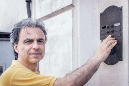 40 years old: Classy  40 years old sportsman with three-day beard and salt and pepper hair wearing a yellow polo shirt while he is ringing a bell of an apartment building in residential neighborhood