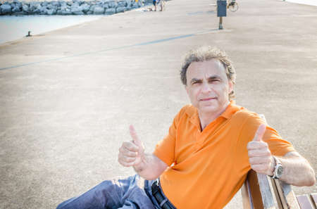 40 years: Classy  40 years old sportsman with three-day beard and salt and pepper hair wearing an orange polo shirt while he is sitting on a bench on the pier and showing thumbs up