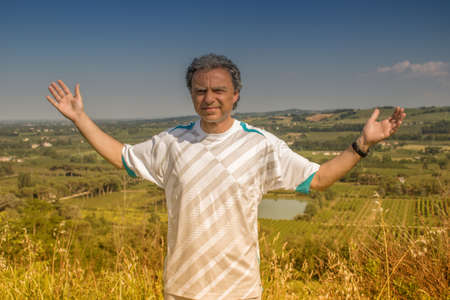 40 years old man: Handsome  40 years old man with salt pepper hair dressed with sports shirt is opening his arms in the cultivated fields of Italian countryside: he shows a reassuring look Stock Photo