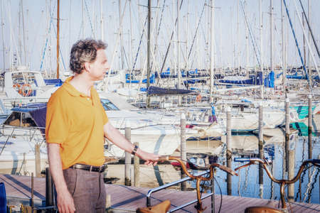 40 years: Classy  40 years old sportsman with three-day beard and salt and pepper hair wearing an orange polo shirt while he is standing in front of the boats moored in the harbor