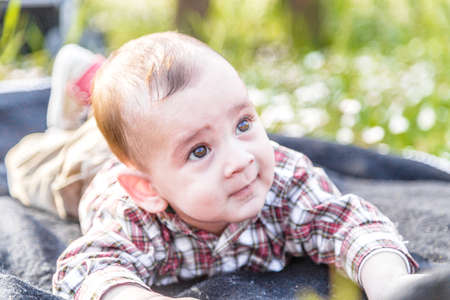 puffing: Funny face of cute 6 months old baby with Light brown hair in red checkered shirt and beige pants: hes biting his lips and puffing cheeks
