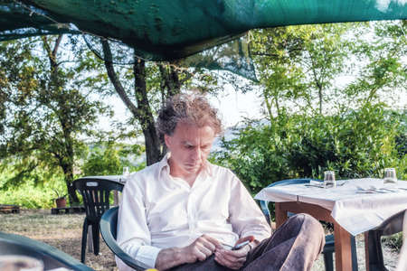 fascinating: fascinating wealthy gentleman of forty coming from city rests on a chair in the garden of a red country house in Italy while using smartphone Stock Photo