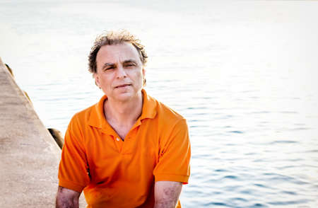 40 years: Classy  40 years old sportsman with three-day beard and salt and pepper hair wearing an orange polo shirt while he is sitting on the pier and resting