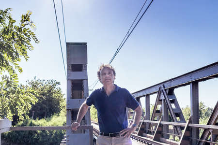 40 years old man: Caucasian 40 years old man, elegant and sporty dressing a blue polo shirt,   next to railroad tracks in the Italian countryside in summer Stock Photo