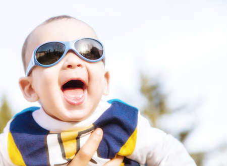 brownish: Cute 6 months old baby with Light brown hair in white, blue and brownish long-sleeved shirt wearing blue googles is embraced and held by his mum: he seems very happy and smiles