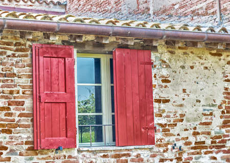 red shutters: Ruins of 15th century country mill, Molino di Scodellino, rustic building made of brick and still working but along dry water channel in Italian countryside. red window with shutters Stock Photo