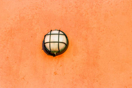 sconce: wall lights with lattice on orange plaster of the outer wall of country house Stock Photo