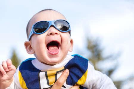 cabello castaño claro: Lindo bebé 6 meses de edad con el pelo marrón claro en camisa de manga larga blanca, azul y marrón que llevaba gafas azules es abrazado y sostenido por su madre: parece muy feliz y sonríe Foto de archivo