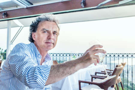 soft skin: Magic moments to share like a quiet dinner at the restaurant overlooking the sea at sunset: nice middle-aged man  with soft skin is going to drink Stock Photo