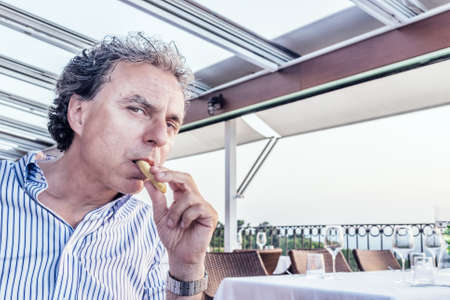 soft skin: Magic moments to share like a quiet dinner at the restaurant overlooking the sea at sunset: funny middle-aged man  with soft skin is eating bread stick