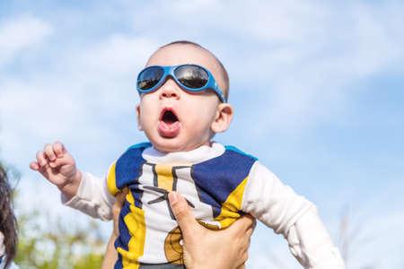cabello casta�o claro: Lindo beb� 6 meses de edad con el pelo marr�n claro en camisa de manga larga blanca, azul y marr�n que llevaba gafas azules es abrazado y sostenido por su madre: parece muy feliz y sonr�e Foto de archivo