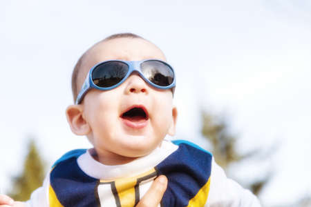 he old: Cute 6 months old baby with Light brown hair in white, blue and brownish long-sleeved shirt wearing blue googles is embraced and held by his mum: he seems very happy and smiles