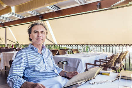 soft skin: middle-aged man  with soft skin in striped shirt looking at the menu of dishes in an outdoor restaurant in summer,