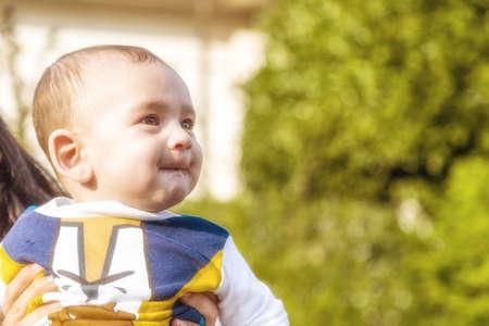 pelo castaño claro: Lindo bebé 6 meses de edad con el pelo marrón claro en camisa de manga larga blanca, azul y marrón es abrazado y sostenido por su madre: él está mordiendo los labios y soplar sus cheecks en una cara graciosa Foto de archivo