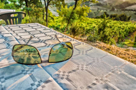 farmlands: see the world through the eyes of ecology - sunglasses with green lenses on a dinner table with vineyards,farmlands and vegetation in the countryside in the background Stock Photo