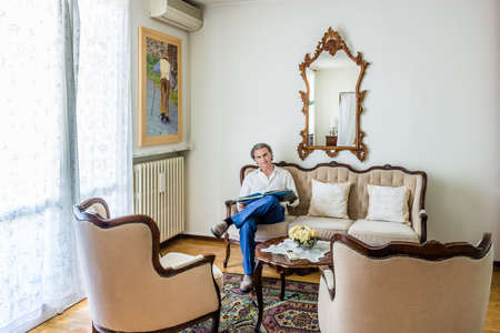 forties: fascinating forties man dressed in a refined yet sporty manner is watching a coffee table photo book on an upholstered sofa in a bright and luxurious living room