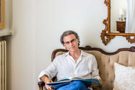 forties: fascinating forties man dressed in a refined yet sporty manner is wearing glasses and watching a coffee table photo book on an upholstered sofa in a bright and luxurious living room