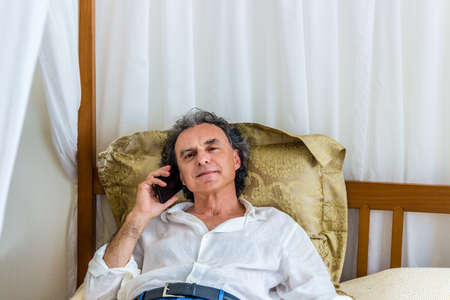 four poster bed: handsome man of forty talking on the phone while resting on a canopy bed without undressing but staying dressed in casual clothing
