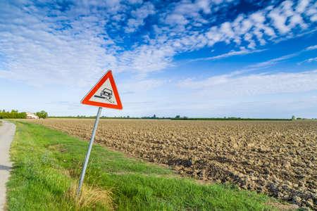 road shoulder: Hazardous Shoulder ruropean road sign along dirt road in Italian countryside on sky background