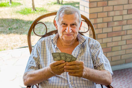 octogenarian: octogenarian elder in checkered shirt is happy while playing cards on the patio of his house in the Italian countryside