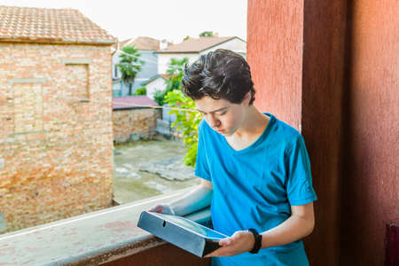 lost in thought: Latin boy lost in thought as his eyes look away toward the tablet PC with a red wall and green leaves as background