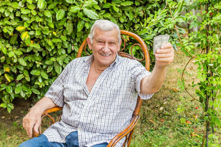 octogenarian: octogenarian elder in checkered shirt is happy while playing cards in the garden of his house in the Italian countryside
