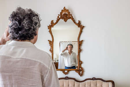 sporty elegant middle-aged man with gray hair is reflected in a large mirror vintage in his living room Stock Photo