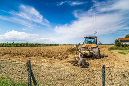 the po valley: the peaceful silence of the fields in the Emilia Romagna region in the lower Po valley in Italy while a tractor is parked in front of the plowed field Stock Photo